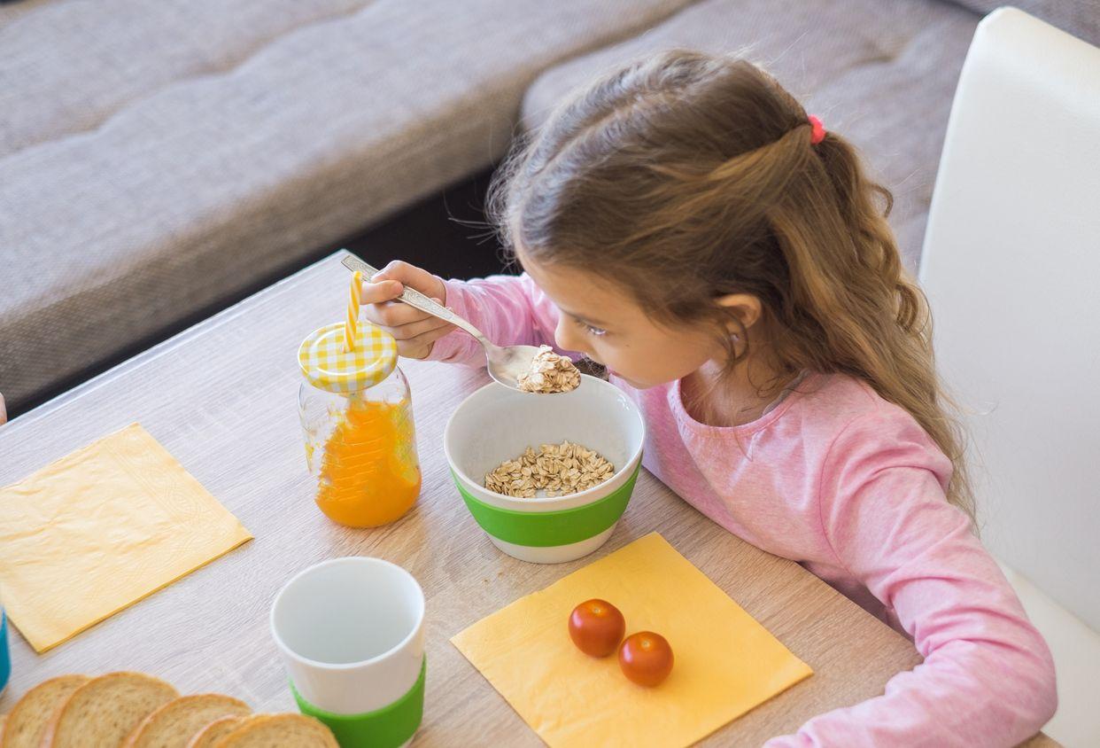 Fille ayant des céréales et des jus de petit-déjeuner.